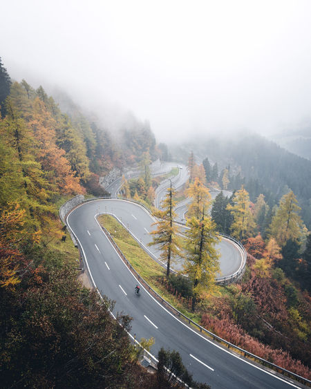 Cycling through the colorful moody paradise Tree Road High Angle View Scenics - Nature Plant Transportation Nature Fog Non-urban Scene Day Beauty In Nature Tranquility Tranquil Scene Autumn Environment Sky Mountain Road Winding Road Outdoors Change Switzerland Maloja Alps Cycling Alpine Pass