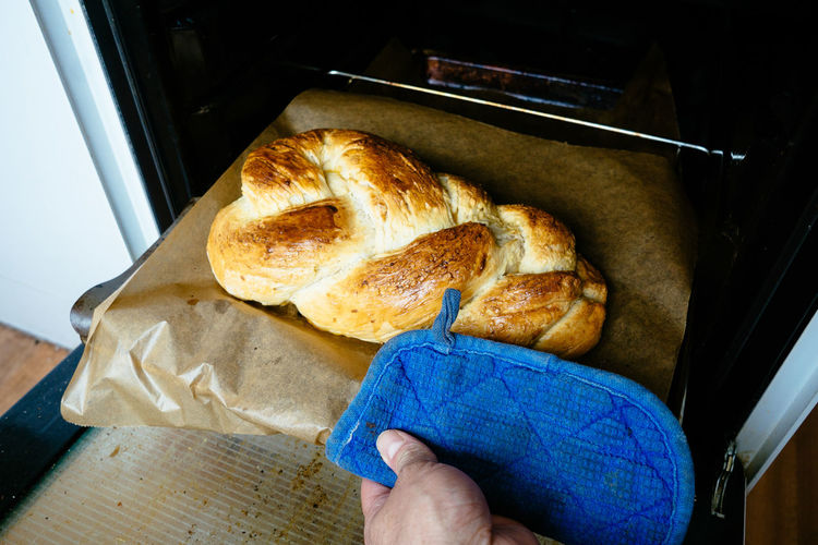 Cropped image of person taking braided bread from oven