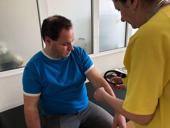 Nurse Examining Man At Hospital