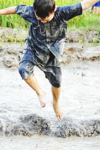 Full Length Of Boy Jumping In Wet Mud