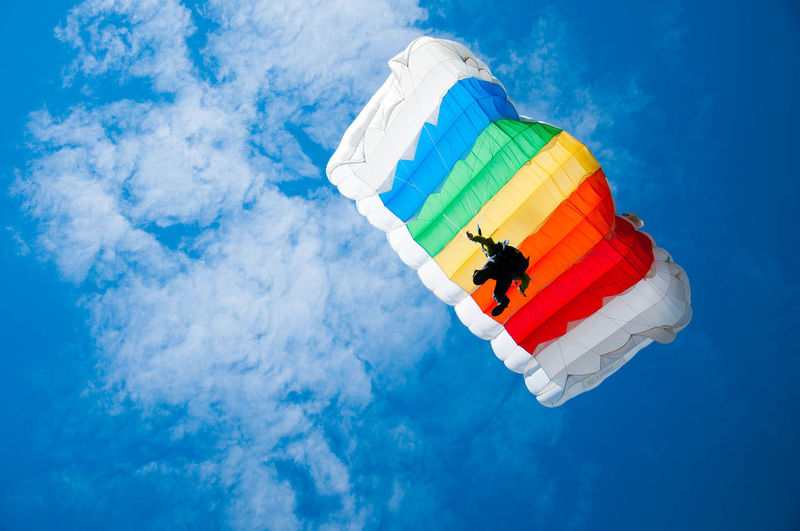 Low angle view of person parachuting against sky