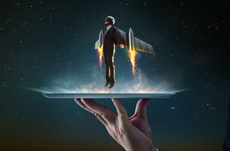 Digital composite image of man flying over digital tablet against star field