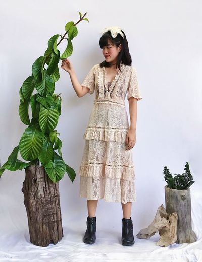 Full length of woman wearing mask standing against plants