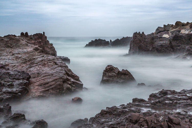 Scenic View Of Rock Formations In Sea Against Cloudy Sky