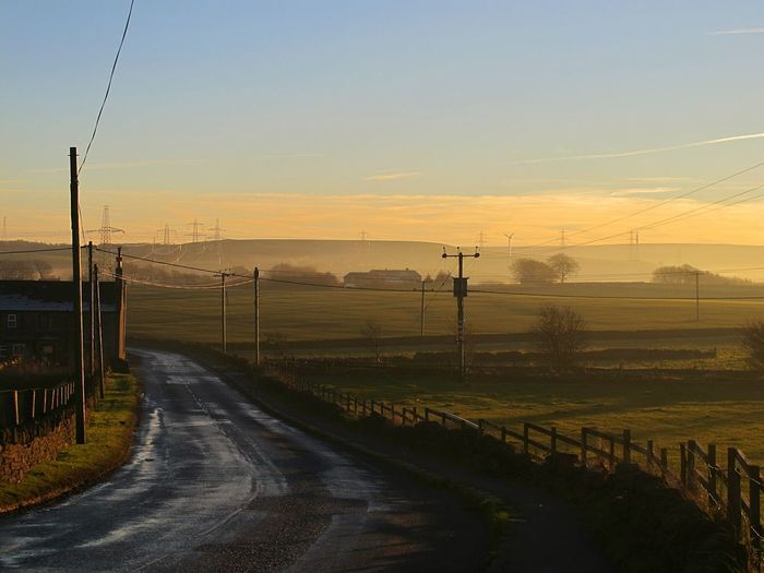 Road amidst field against sky during sunrise