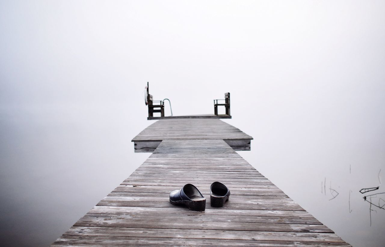 Footwear on wooden pier over calm lake