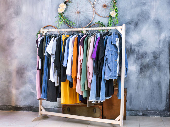 Multi colored clothes hanging on rack at home