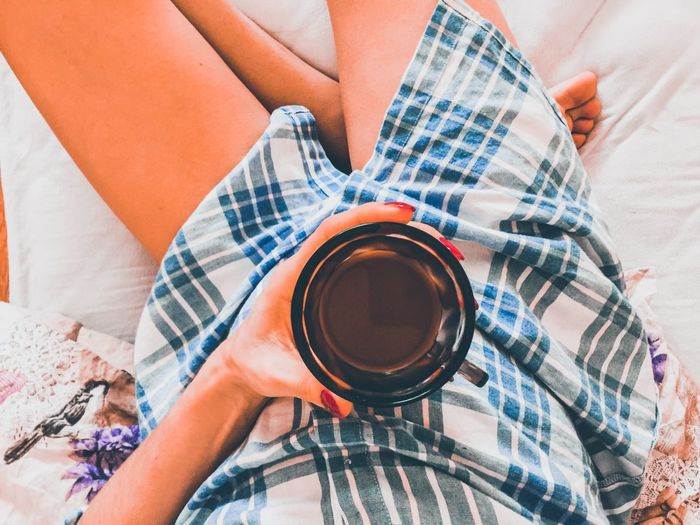 Low section of woman drinking coffee on bed