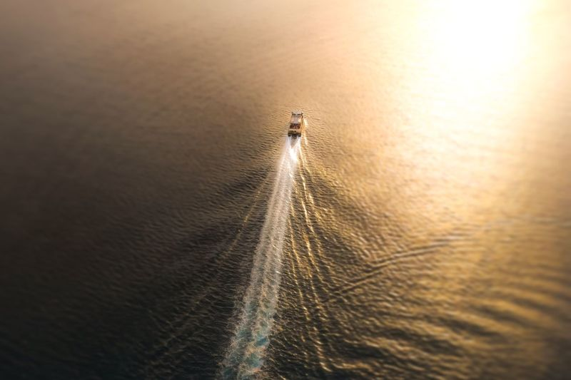 High angle view of boat moving on sea during sunset