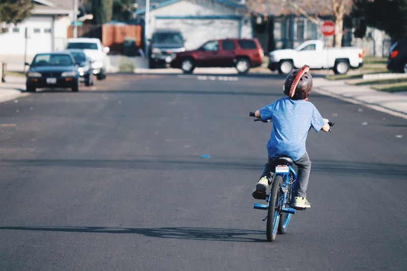Rear view of boy riding bicycle on street