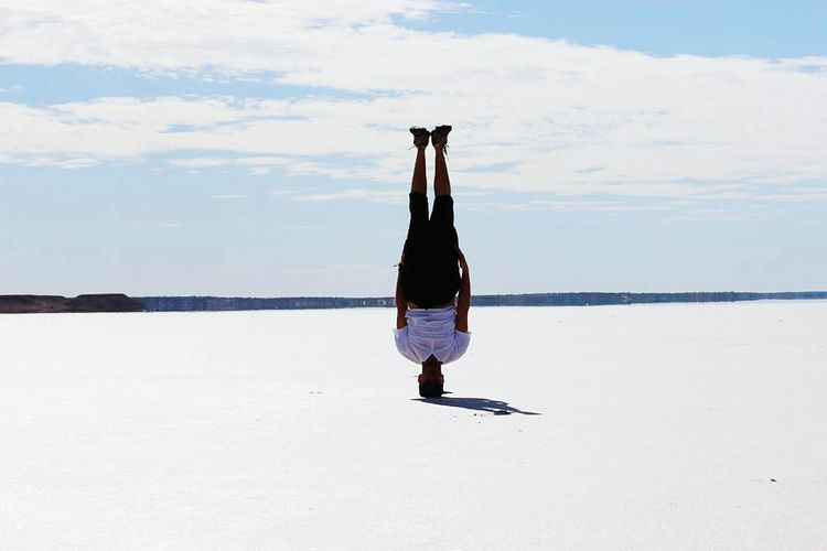 Full length of man doing headstand on salt flat against cloudy sky