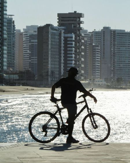 Apreciando Bicycle One Man Only One Person City People Silhouette Adult Full Length Water Outdoors Business Day Architecture Sky Sun Photographing Cearaemfotos Igersbrasil IgersCeará Beauty In Nature Photography Themes Ceará Beach Tourism Travel Destinations