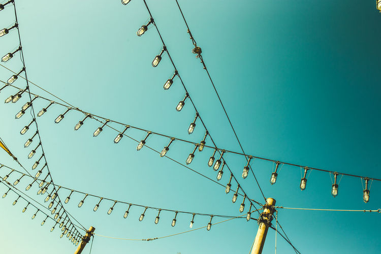 Low angle view of lights hanging against clear blue sky
