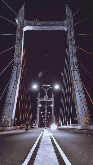 Surface level of suspension bridge against sky at night