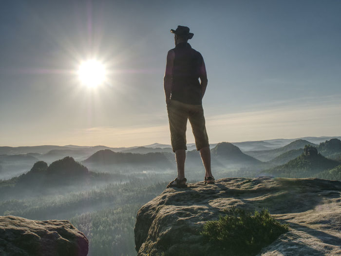 Tall man in shorts wearing cowboy hat shielding his face from sun, watching over large valley bellow