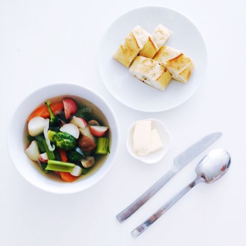 High Angle View Of Vegetable Soup And Baguette By Butter On White Table