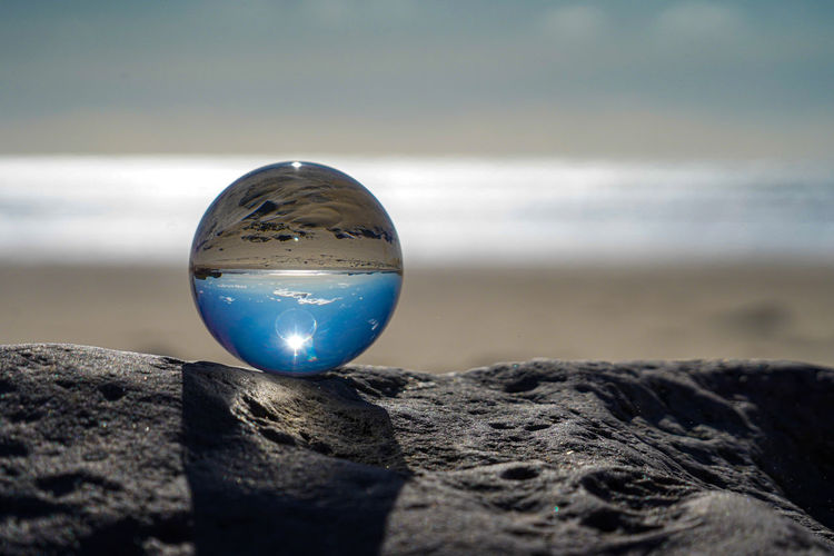 Close-up of crystal ball on beach against sky