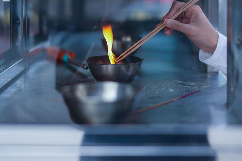 Cropped Hand Igniting Incense Sticks In Bowl Seen Through Glass