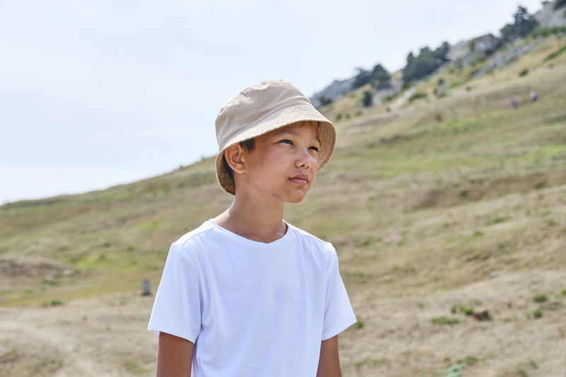 Half-length portrait of an asian boy in a white t-shirt and a panama hat on a background of nature.
