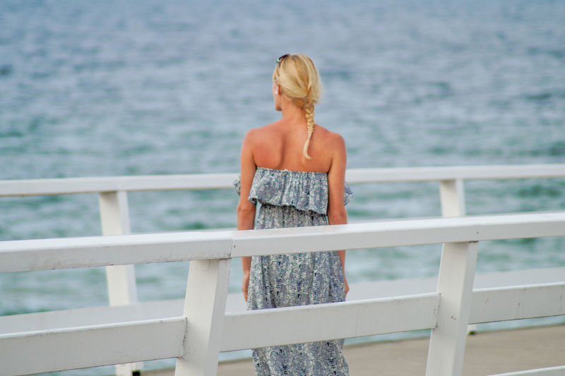 Rear view of young woman standing on pier over sea