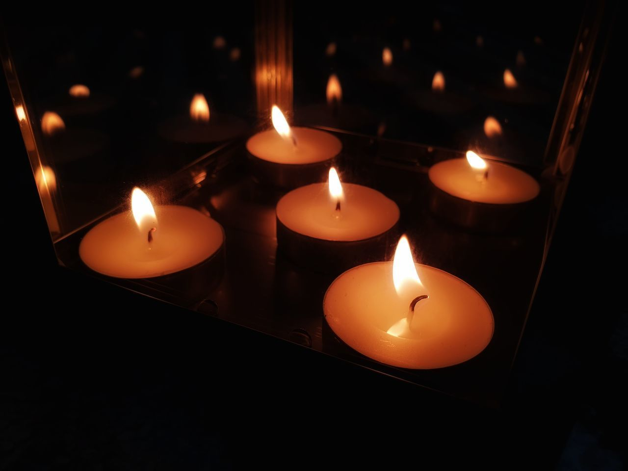 CLOSE-UP OF LIT CANDLES IN DARK ROOM