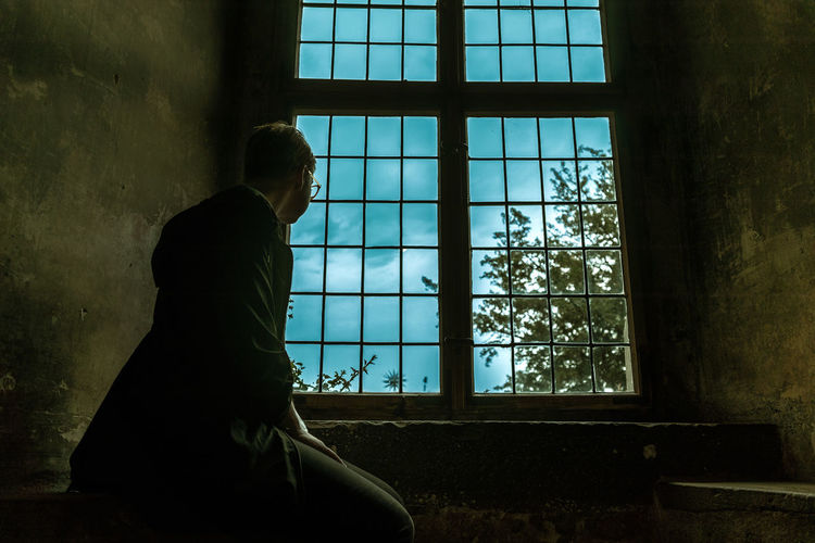 Side view of young man looking through window