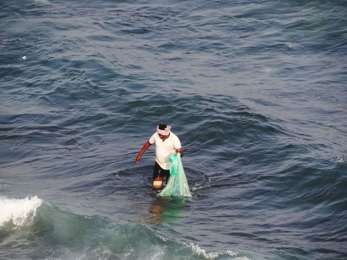 High angle view of man wading in sea