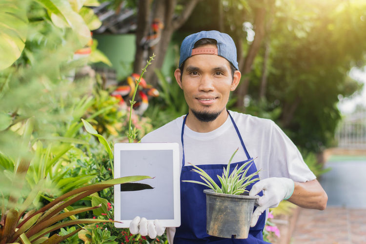 Portrait of smiling young man holding potted plant