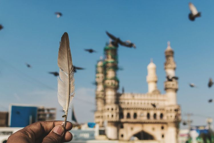 Cropped hand of man holding feather against char minar