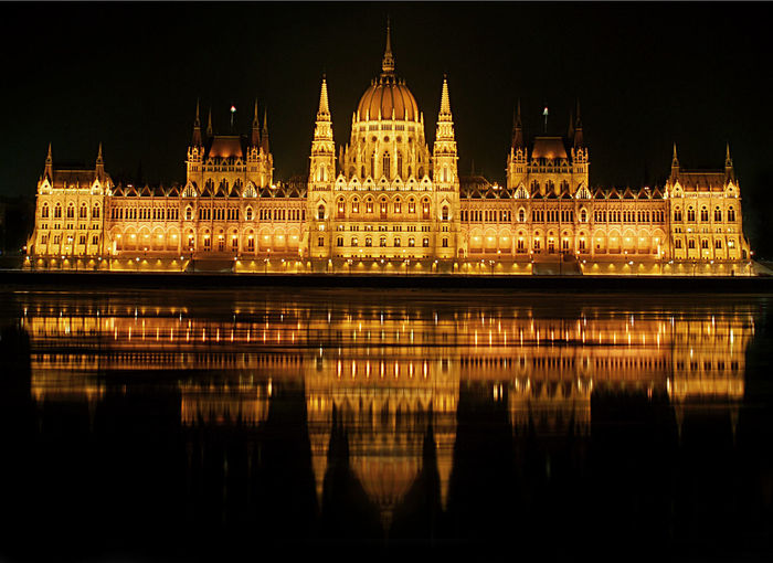 Reflection of illuminated building in calm river
