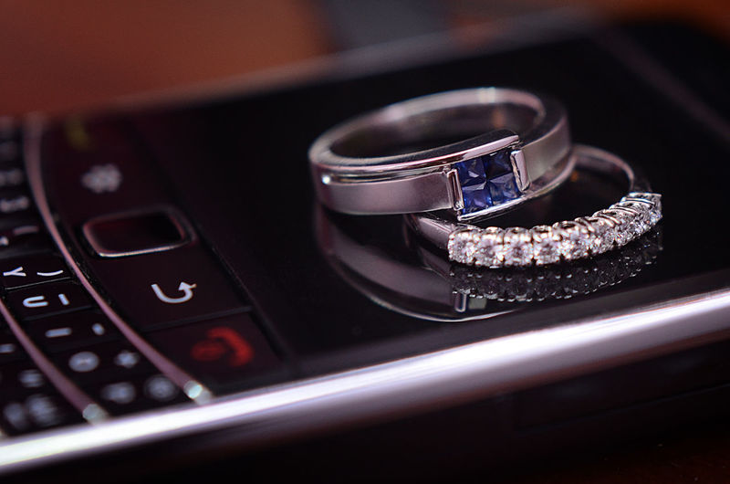 Close-up Of Wedding Rings On Cellphone
