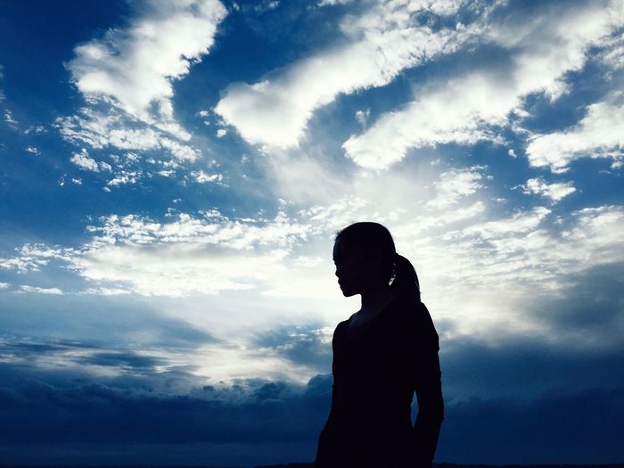 Silhouette woman standing against cloudy sky