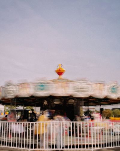 Blurred motion of people at amusement park against sky