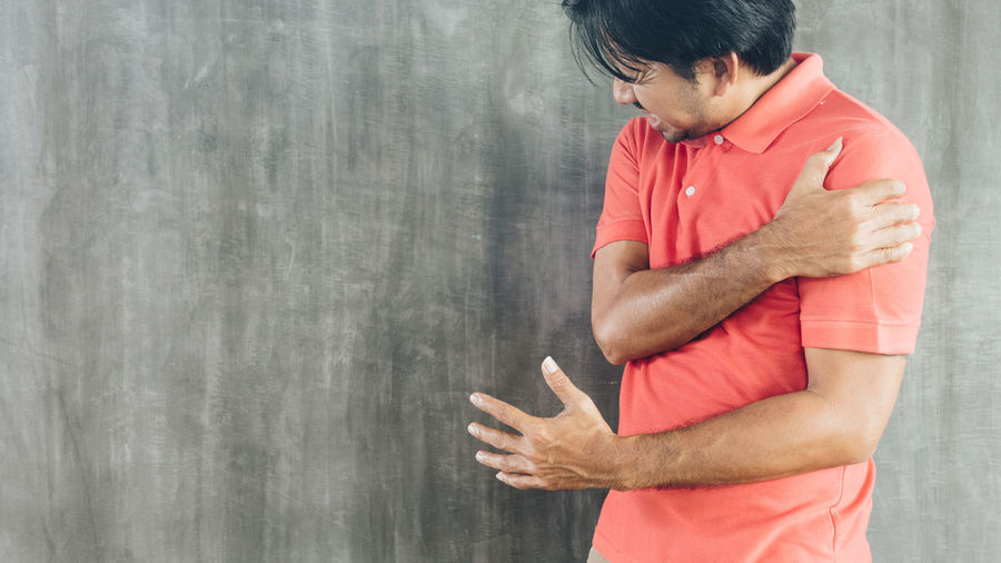 Side view of man standing against wall