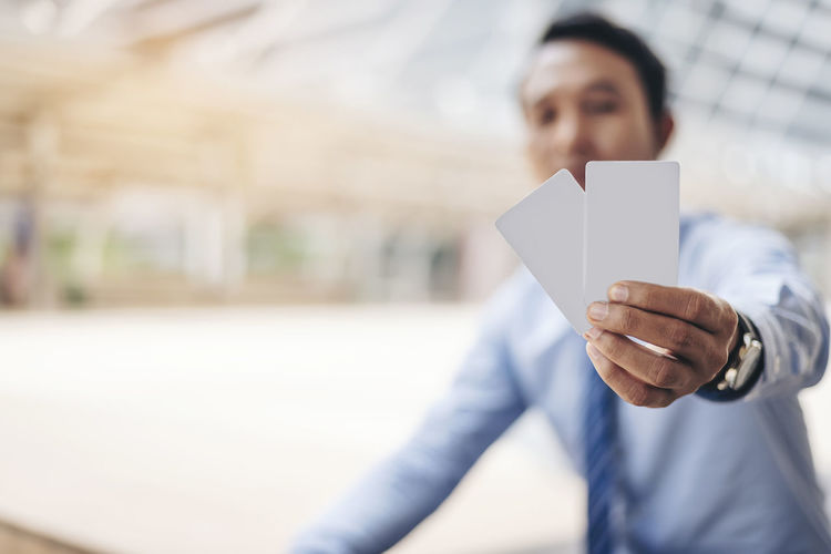 Businessman Holding Cards In City