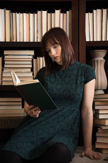 Young woman reading a book Publication Book Education Learning Bookshelf Studying Young Adult Young Woman Adult College Bookworm Indoors  Real People Young Women One Person Lifestyles Sitting Women Reading Literature Reading Hard Cover Books