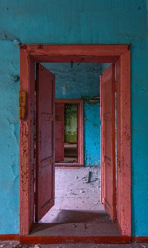 Abandoned double doors open doorway interior in blue-orange colors.