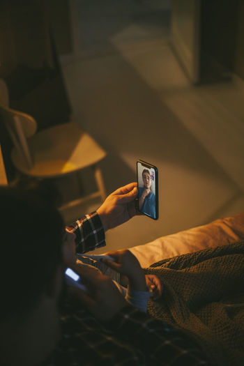 Man using smart phone on bed at home