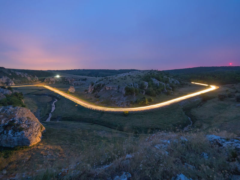 Sky Road Transportation Nature Landscape Sunset Illuminated Dusk Environment Night Speed Mountain Twilight Outdoors Valley Tourism Scenics - Nature Travel Blue Sky Light Trails Way Rocks Hill Beauty Evening