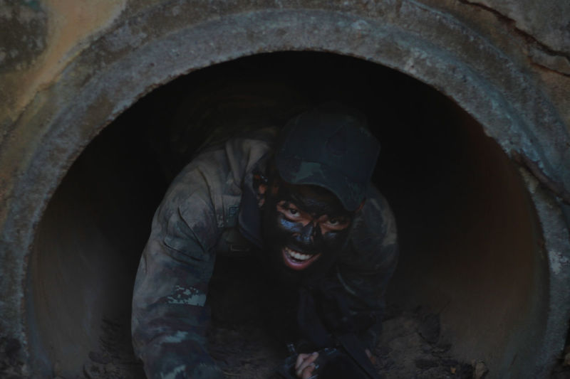Portrait Of Smiling Man With Dirty Face In Concrete Pipe