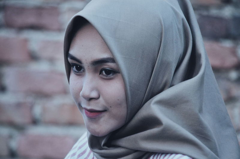 Close-up of woman wearing hijab against brick wall