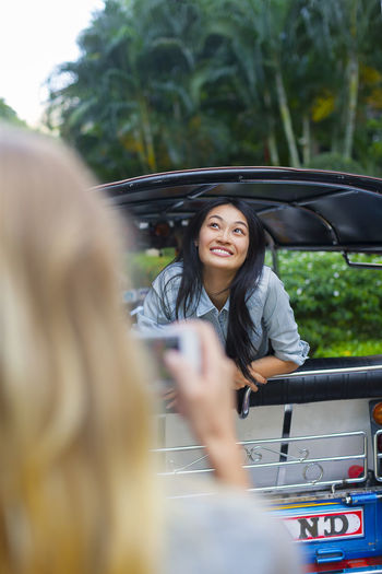 Young woman using phone while sitting on car