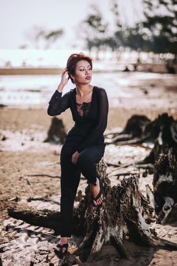 Thoughtful woman sitting on tree stump at beach