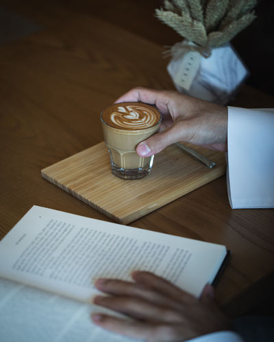 Coffee on Wooden Table with Book in Cafe Ijas Muhammed Photography Table Drink One Person Human Hand Paper Hand Holding Food And Drink Publication Book Indoors  Real People Coffee Cup Refreshment Mug Coffee - Drink Cup Pen Coffee Glass Crockery Drinking