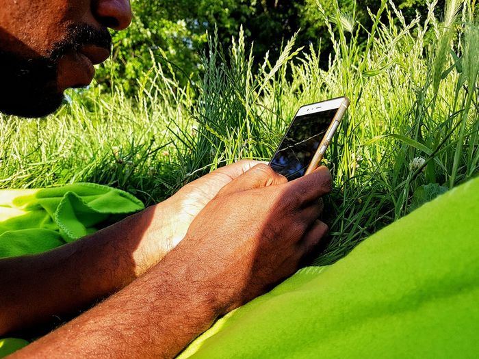Green Green Color One Person Real People Human Body Part Close-up Grass Tree Nature Human Hand Cellphone Man With A Phone Technology Communication Mobile Phone Outdoors Man In The Park Man Using His Phone Internet Searching Man's Hands Black Man Face Part