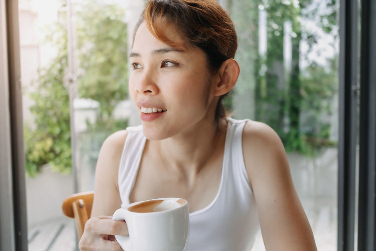 Portrait of young woman drinking coffee cup