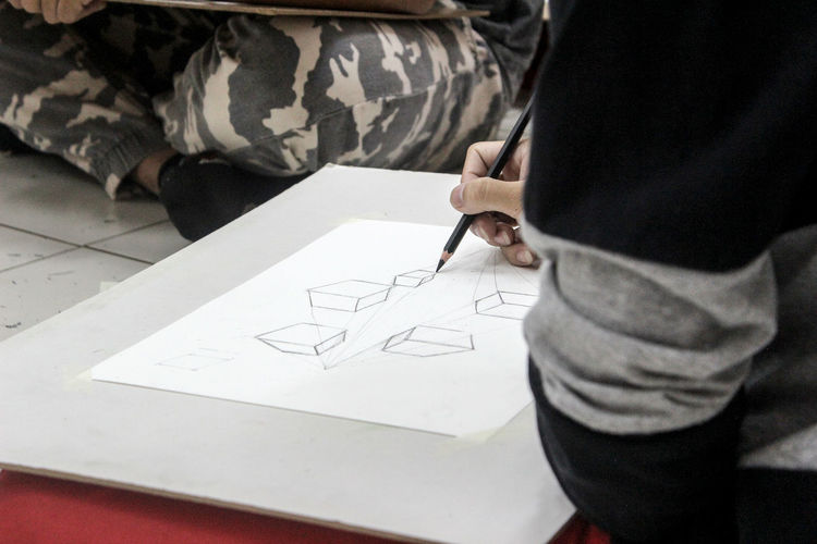 Architecture Art And Craft Casual Clothing Creativity Drawing - Activity Drawing - Art Product High Angle View Holding Indoors  Midsection One Person Paper Pen Pencil Real People Sketch Standing Table Writing