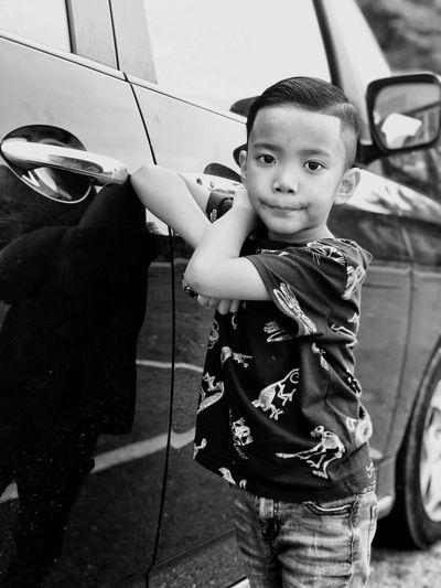 Portrait of cute boy standing by car