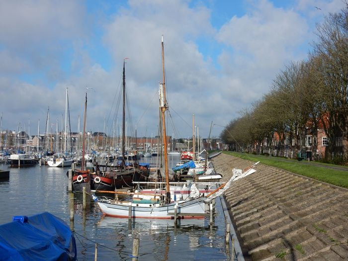 Sailboats Moored At Hoorn Harbor Against Sky