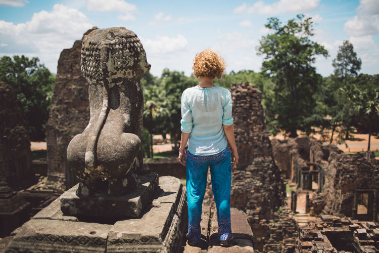 Rear View Of Woman Standing By Old Statue At Temple Against Sky